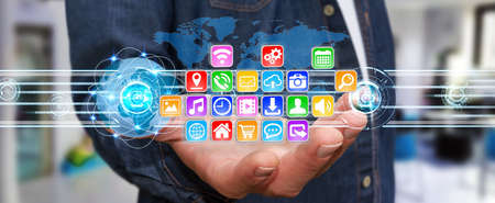 business globe: Young man holding application icons interface in his hand