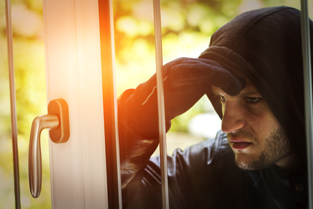 delinquency: Burglar wearing black clothes and leather coat breaking in a house
