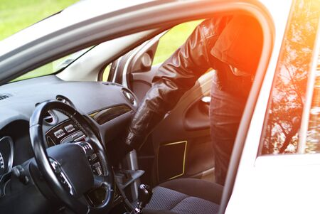nuisance: Thief wearing black clothes and leather coat stealing a car Stock Photo