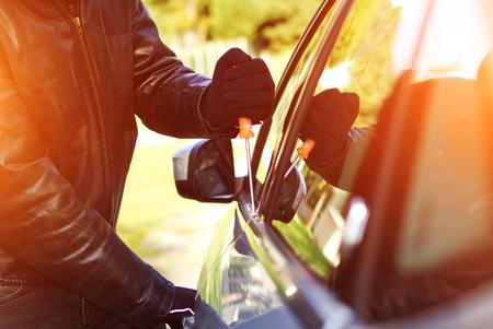 Ladrón que desgasta la ropa negra y abrigo de cuero robar un coche