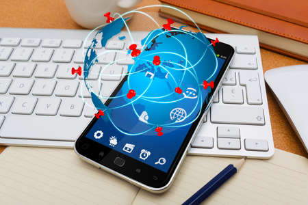 for: Modern mobile phone in office with travel icon application flying over