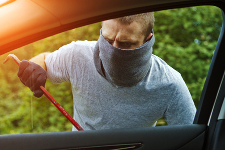 thief: Thief wearing black clothes and leather coat stealing a car Stock Photo