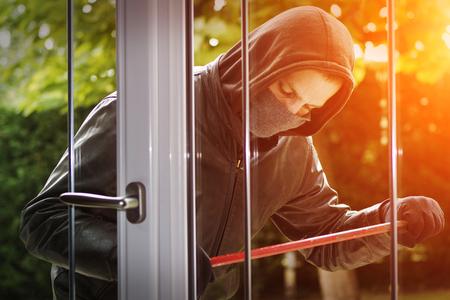 Ladrón llevaba ropa negra y abrigo de cuero de última hora en una casa Foto de archivo - 52625730