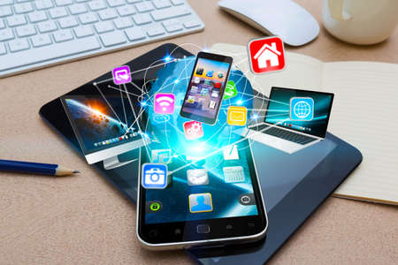 Modern mobile phone in office connecting tech devices together Stock Photo