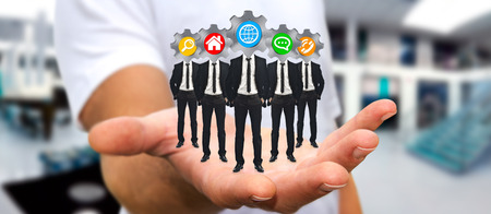 net meeting: Young man holding in his hand group of businessmen working together as a team with icons instead of their heads Stock Photo