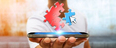 smart investing: Businessman in his office with puzzle pieces flying over his mobile phone