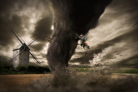View of a large tornado destroying a barn