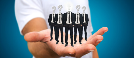 connexion: Young man holding in his hand group of businessmen working together as a team with icons instead of their heads Stock Photo