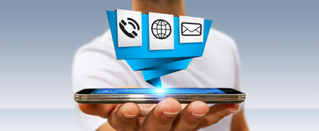 connexion: Young businessman holding modern digital origami icon application over his mobile phone