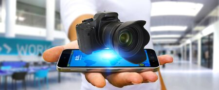 connexion: Young man holding modern digital camera over his mobile phone Stock Photo