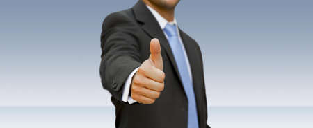 affirmative: Businessman at the office with his thumb up