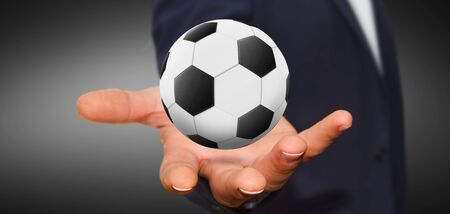 Business man holding back and white football in his hand Stock Photo