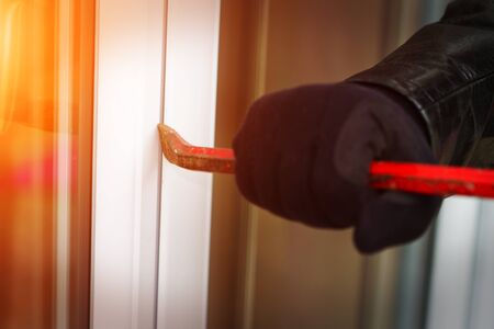 insecurity: Burglar wearing black clothes and leather coat breaking in a house