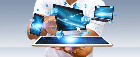 computer devices: Businessman connecting tech devices computer phone and tablet