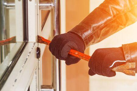 delincuencia: Antirrobo tratando de entrar en una casa con una barra de hierro