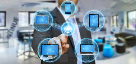 connexion: Businessman connecting tech devices computer phone and tablet