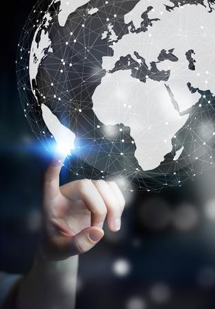 Zakenvrouw in donker kantoor met behulp van een digitale tactiele wereldinterface met zijn vinger