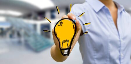 Business woman drawing lightbulb with a pen