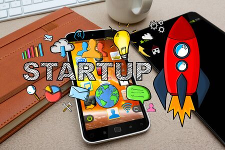 Startup presentation with rocket and icons on desk office background Stock Photo