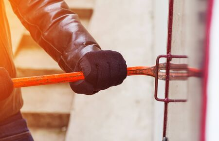 delinquency: Burglar trying to break into a house with a crowbar