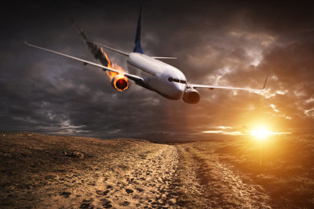 explosion engine: White plane with engine on fire about to crash in the landscape Stock Photo