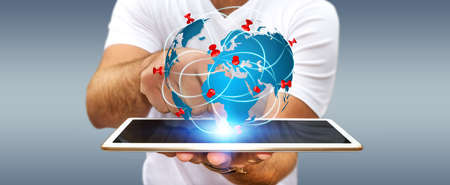 Businessman with digital world map and pins floating over his tablet Stock Photo