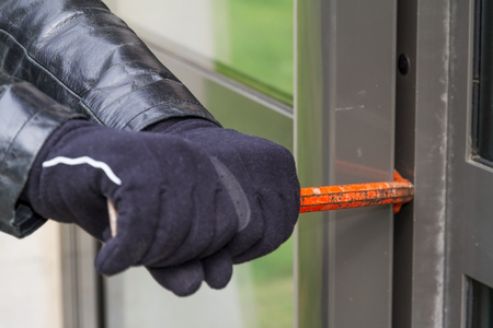 delinquent: Burglar trying to break into a house with a crowbar
