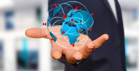Businessman with digital world map and pins floating over his hand Stock Photo