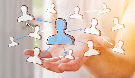 connexion: Businessman on blurred background holding hand drawn social network in his hand Stock Photo