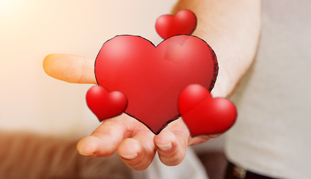 Young man holding hand drawn red heart in his hand on blurred background Stock Photo