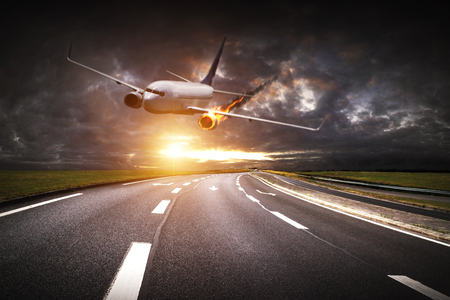 explosion engine: White plane with engine on fire about to crash on a road Stock Photo