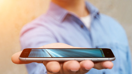Businessman holding modern mobile phone in his hand on blurred background