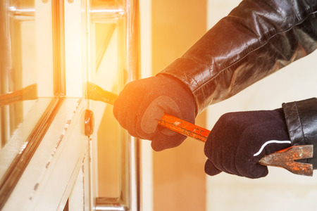law breaking: Burglar trying to break into a house with a crowbar