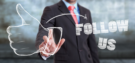 Businessman on blurred background touching hand drawn thumb up sketch Stock Photo