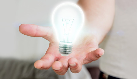 Businessman on blurred background holding shiny lightbulb in his hand �3D rendering�