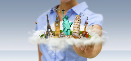 Young woman holding a cloud full of famous monuments of the world in his hands