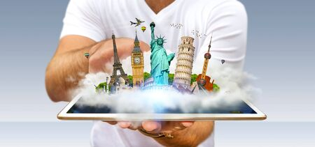 Young man holding a cloud full of famous monuments of the world over his digital tablet