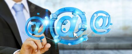 Businessman on blurred background touching 3D rendering email icon with his finger