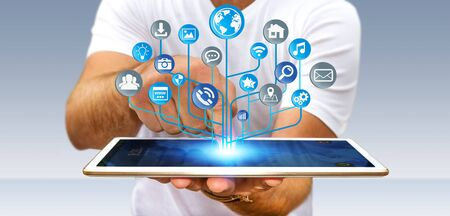 Young businessman holding modern digital electronic circuit with icons over his mobile phone