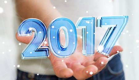 Businessman holding blue 2017 3D rendering transparent text in his hand Stock Photo