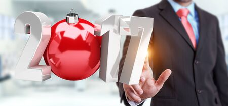 Businessman touching 2017 3D rendering text with christmas ball with his finger