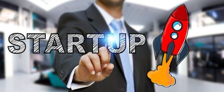 Businessman on blurred background touching hand drawn startup text and red rocket with his finger