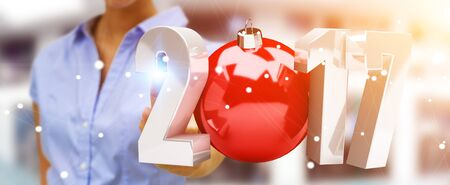 silver: Businesswoman touching 2017 3D rendering text with christmas ball with her finger Stock Photo