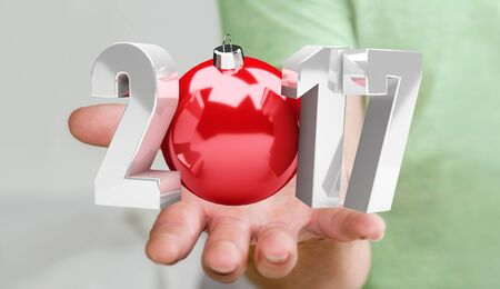 Businessman holding 2017 3D rendering text with christmas ball in his hand