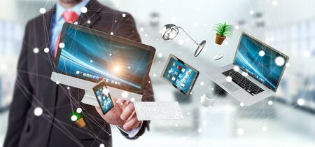 Businessman on blurred background touching flying desk laptop phone and tablet with his finger 3D rendering Stock Photo
