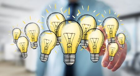 Businessman on blurred background touching hand-drawn lightbulb with his finger