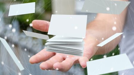 contact: Businessman holding white floating business card in his hand 3D rendering Stock Photo