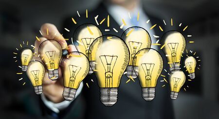 Businessman on blurred background drawing a lightbulb with a pen