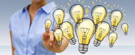 Businesswoman on blurred background touching hand-drawn lightbulb with her finger Stock Photo