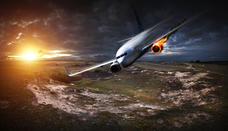 malfunction: White plane with engine on fire about to crash in the landscape Stock Photo